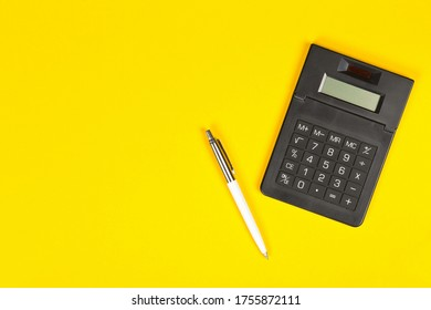 Pocket calculator with pen on yellow background with copy space - minimal modern tax, finance or accounting concept, top view flat lay from above