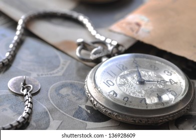pocket clock with  chain on background of old photos
