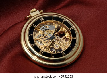Pocket clock in gold showing the mechanism on red fabric
