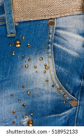 Pocket jeans with rhinestones and gold belt. Close-up