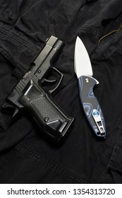 Pocket knife and pistol. Weapons on a black background.