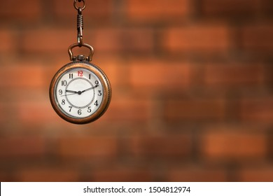 Pocket watch against blurred red brick wall. Time concept with copy space. Retro clock. Selective focus