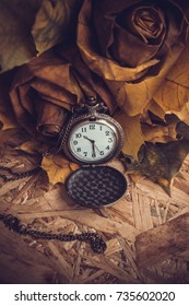pocket watch and autumn leaves on a wooden table