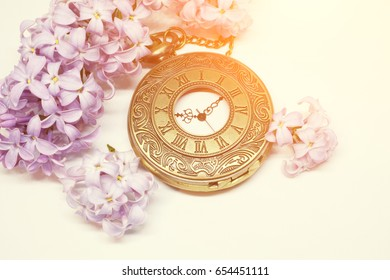 Pocket watch and beautiful lilac flower on white background. Toned photo