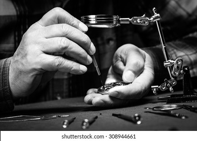 Pocket watch being repaired by senior watch maker, close-up. Black and white.