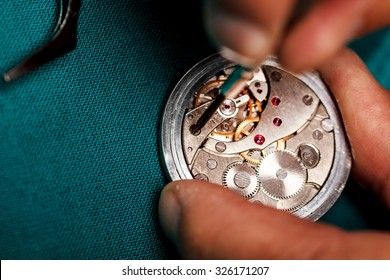 Pocket watch being repaired by senior watch maker, close-up.