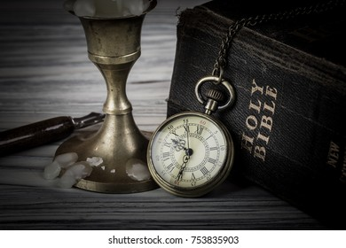 Pocket watch candle and Holy Bible