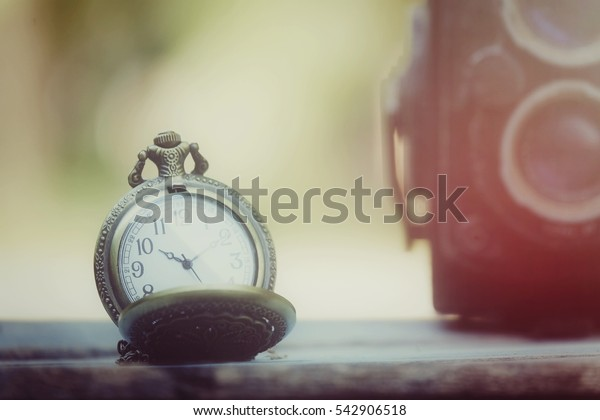 Pocket watch and classic camera on wood table, process vintage tone