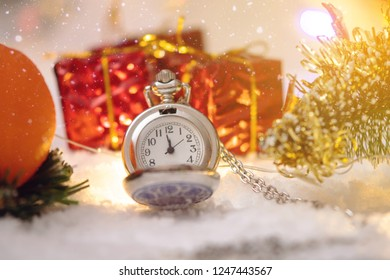 Pocket watch with a dial in the snow with gifts on the eve of holidays. Concept waiting for the magic of Christmas and new year