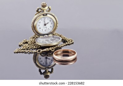 Pocket watch and a gold wedding ring on a reflective surface