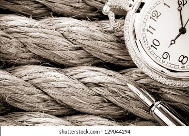 pocket watch with ink pen on ship ropes