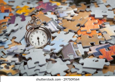 Pocket watch on a pile of jigsaw puzzle pieces. Shallow depth of field