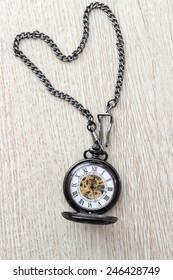 pocket watch on  wooden table, from above