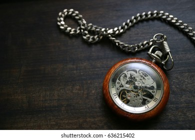 A pocket watch placed on a black wood grain board. Image with character space.