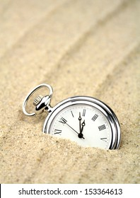 Pocket watch semi buried in the sand