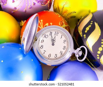 Pocket watch showing almost twelve o'clock (five minutes to the midnight) and multicolored Christmas balls, New Year concept