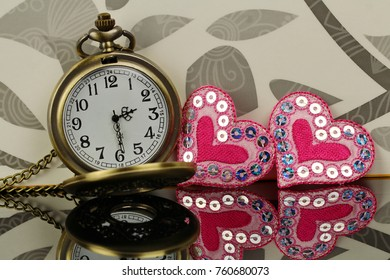 A pocket watch with two decorative hearts