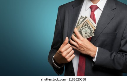 Pocketing company money. businessman placing money into