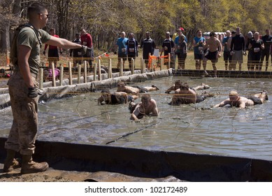 POCONO MANOR, PA - APR 29: A man directs participants crawling under electrified wires at Tough Mudder on April 29, 2012 in Pocono Manor, Pennsylvania. The course is designed by British Royal troops.