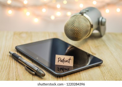 Podcast concept with mic and shiny black tablet