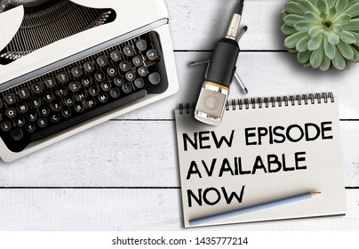 podcast concept, top view of microphone on desk with old typewriter and notepad with text NEW EPISODE AVAILABLE NOW