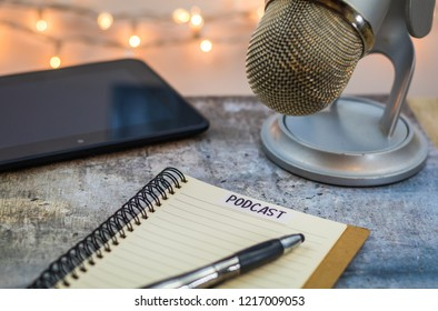 Podcast idea concept with microphone, notepad, table, on wooden board