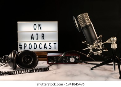 """Podcast studio set with microphone, headphones, console and """"on air"""" sign turned on, over marble table and black background."""