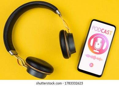 podcasting concept, above view of headphones and smartphone with podcast player mockup on yellow background