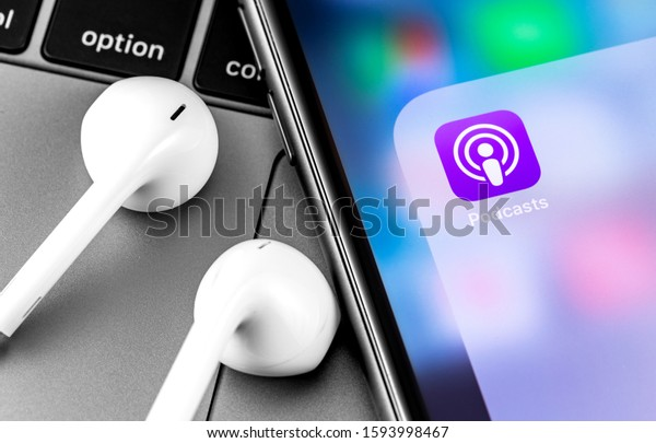 Podcasts icon app on the screen Apple iPhone and Earpods headphones. Apple Inc. is an American multinational technology company. Moscow, Russia - April 10, 2019