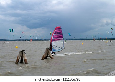 Podersdorf am See, Austria - June 23, 2018: Neusiedler see lake view with surfers, winsurfers, water sports activities.