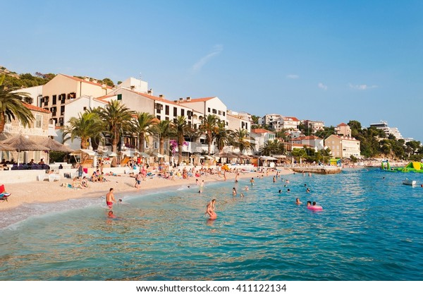 PODGORA, CROATIA - JULY 20, 2013: People swim and sunbathe at the amazing beach of Podgora with hotel Podgorka in background. Podgora is a popular holiday resort in Croatia.