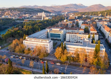 Podgorica Montenegro in autumn: President and Parliament buildings, white in the first row, and Government in the grey one behind. Yellow foliage on the main street in the afternoon, close to sunset. - Shutterstock ID 1865305924