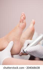 podiatrist ( chiropodist ) cleaning womans feet ( toenails )