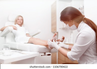 Podiatrist female doctor making procedure of massage and peeling feet with for smiling blondie client. Happy woman relaxing at beauty salon, caring about her health. Podiatry and beauty service.