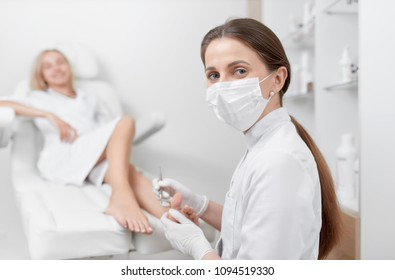Podiatrist female doctor in mask on face, looking at camera and making procedure for foot with special equipment. Pretty blondie client spanding time at beauty salon, caring about her health.