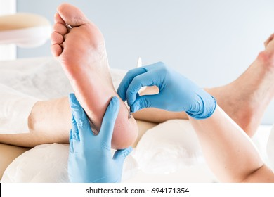 Podiatrist treating toenail fungus. Podology treatment.