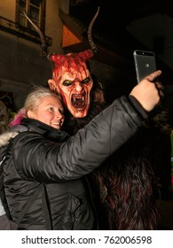 "PODKOREN, SLOVENIJA - NOVEMBER 24th 2017: The woman taking a selfie with the Krampus (devil) at traditional procession  ""Parkelj gathering"" in Podkoren, Slovenia"