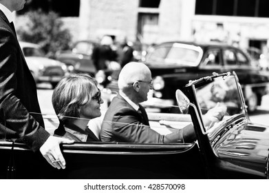 Podol, Ukraine - May 19, 2016: Elegant people on sunglasses with cigarette stay  on Maybach Cabriolet, luxury classic car. Black and white photo