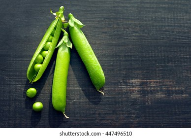 Pods of green peas and pea on a dark wooden surface, top view