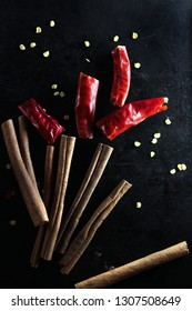 pods of red Chili pepper and cinnamon sticks on dark background