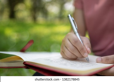 poem, poetry and knowledge education concept,  close up sitting writing on notebook in park