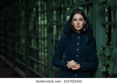 Poetic beautiful brown hair brunette woman or girl in old vintage classic dress coat looks camera by green eyes and holds hands together laying on backyard garden park iron forged fence