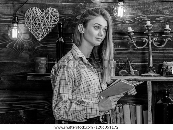 Poetry evening concept. Girl reading poetry in warm atmosphere. Lady on dreamy face in plaid clothes holds book, reading poetry. Girl in casual outfit in wooden vintage interior enjoy poetry.