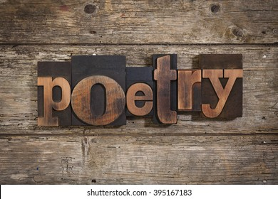 poetry, single word set with vintage letterpress printing blocks on rustic wooden background