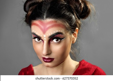 Pofrtrait fashion young model. Red dress.Futuristic makeup art. Top knot hairdo.Perfect beaty skin.closeup.Gray background