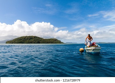 Pohnpei, Micronesia - Dec 27,2011: a local Micronesian man in a boat pulls a buoy out of the water with Pohnpei island in the background, Caroline islands, Federated States of Micronesia (FSM)