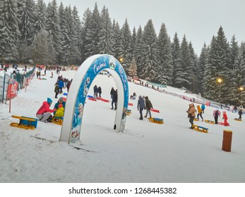 Poiana Brasov, Romania - December 26, 2018: Crowds of people come to Poiana Brasov resort during the winter holidays to ski, sled or enjoy a snowboard slide down the slopes.