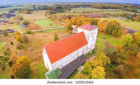The Poide church on top of the hill surrounded with green grasses and trees in the small village of Poide in Saaremaa Estonia