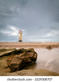 Point Of Ayr Lighthouse At Talacre Beach aginst a cloudy sky.
