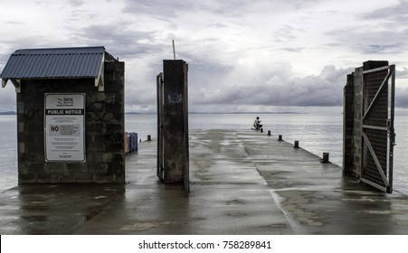 """Point Cruz Ports Authority, Honiara,Solomon Islands, Nov. 2017, a lonely man sits at the jetty of the Honiara port overlooking the """"Iron Bottom Sound"""" where a big naval battle happened in WW II"""